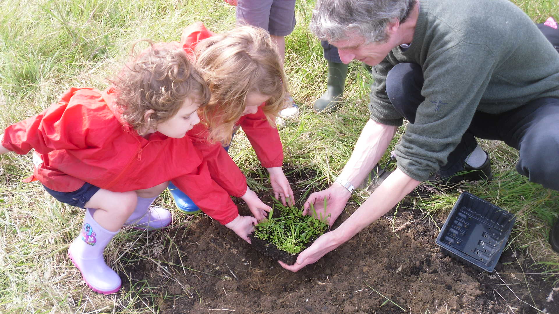 Mark Bianco helps children from the Histon Early Years Centre plant their wildflowers